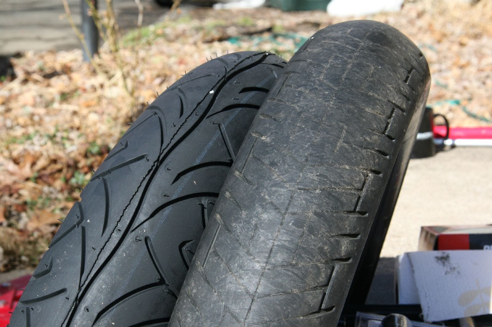 a brand new tyre next to a well worn tyre