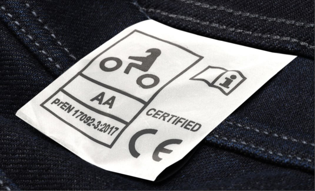 A close up of a CE certified tag on a pair of Macna jeans