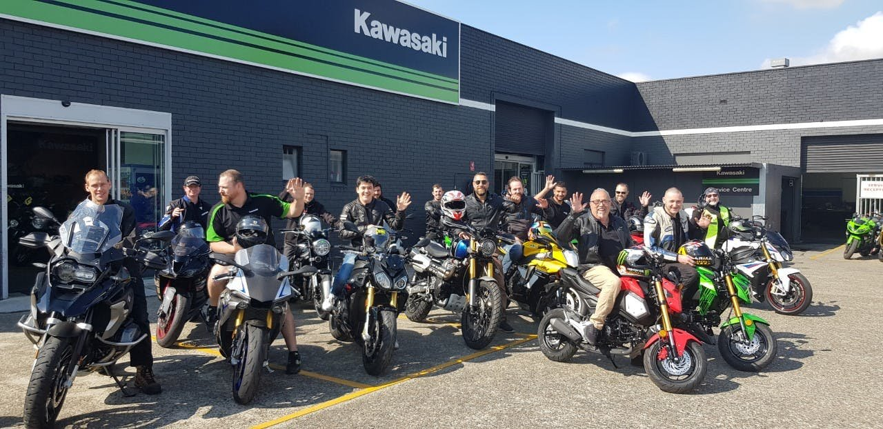 About 20 people sitting on motorcycles in front of a motorcycle shop smiling and waving