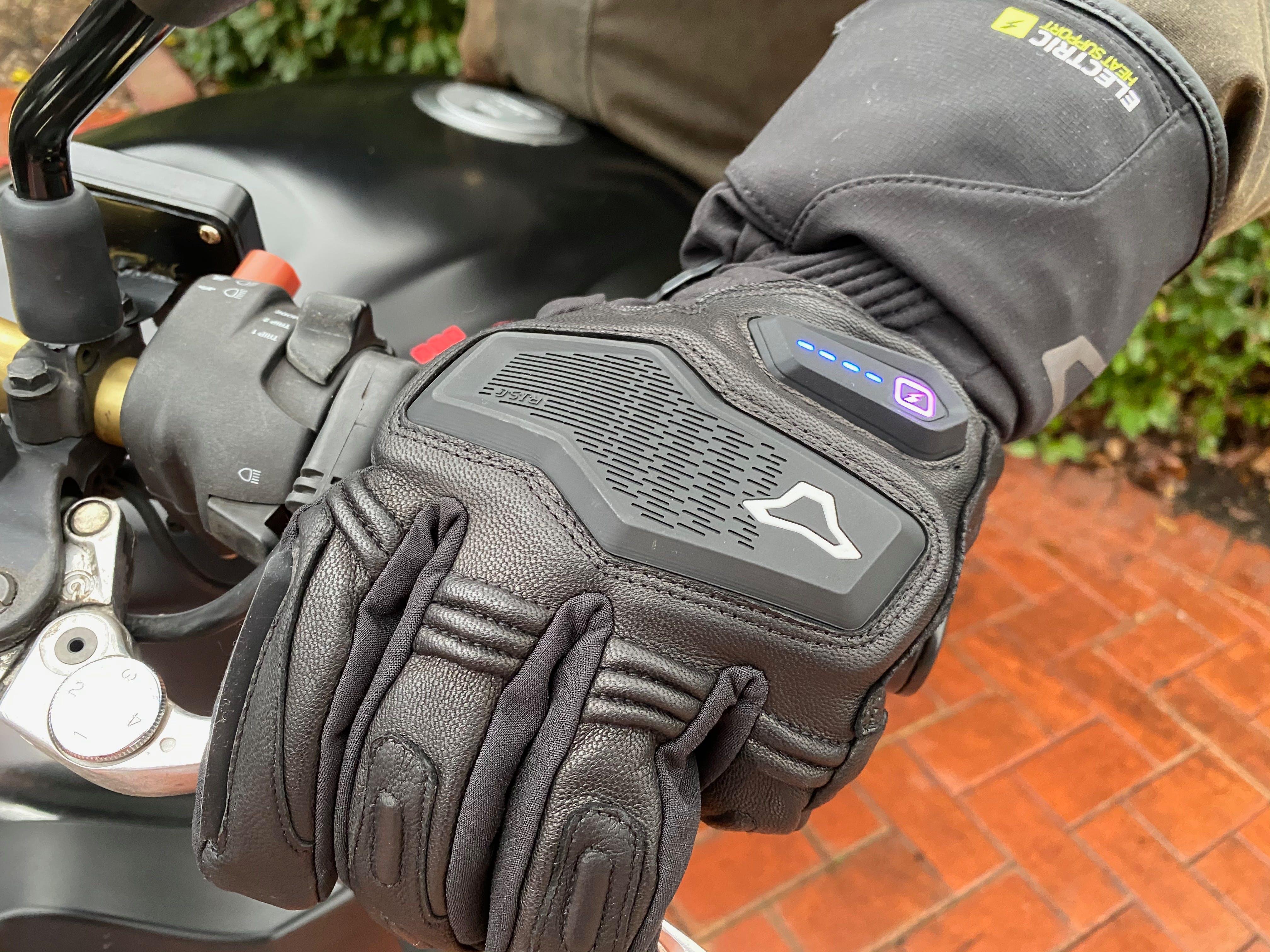 The Macna Ion heated glove on a mans hand on a motorcycle handlebar