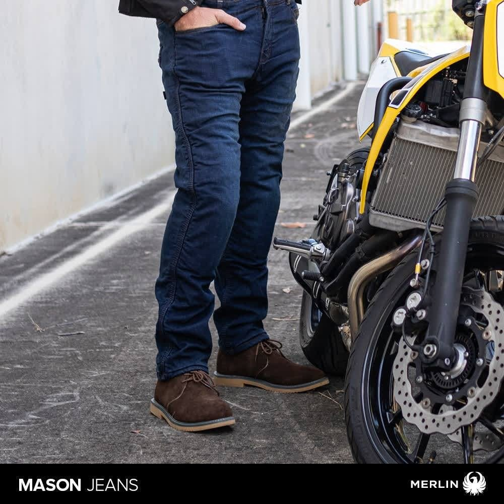 Man wearing the Mason jeans by Merlin next to a yellow motorcycle