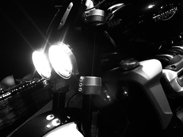 Black and white photo of headlights on Triumph Rocket 3R lit up with the Opera House behind it