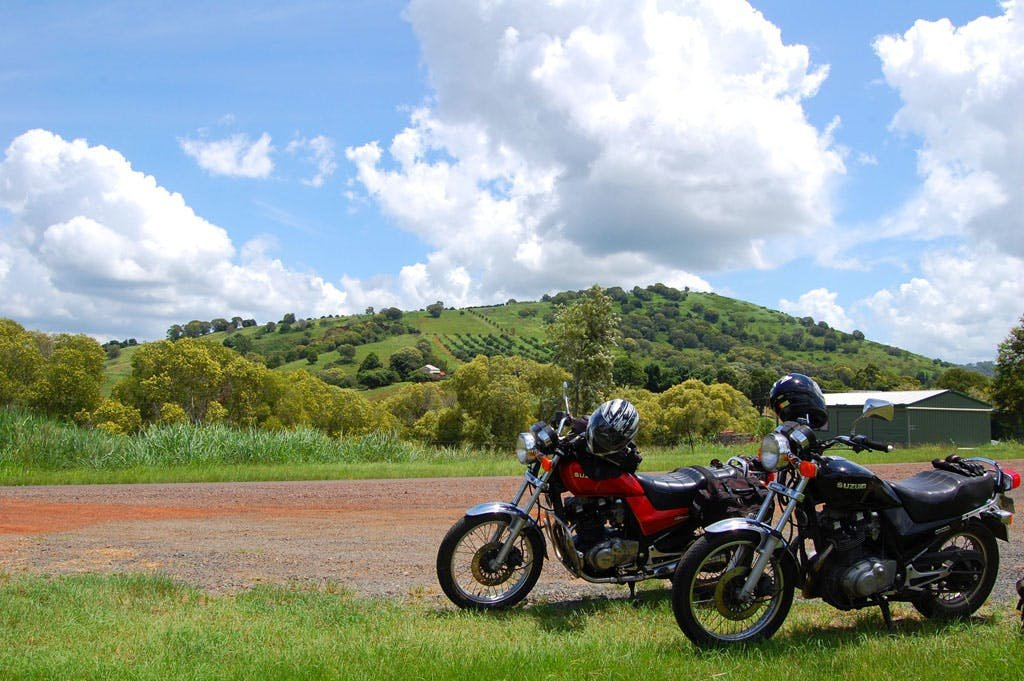 a black and a red motorcycle near a dirt road on a sunny day with clean skies and white clouds