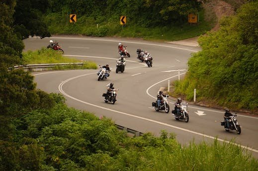 A few riders on a windy road