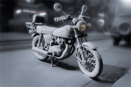 A frozen motorcycle covered in snow on a frozen street