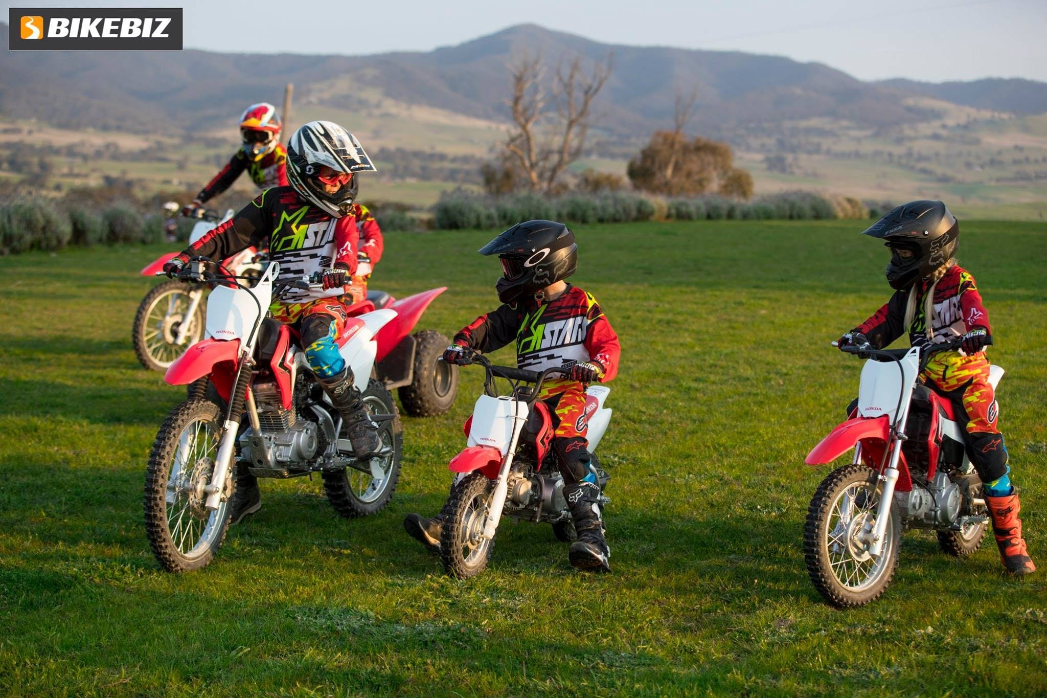 2 kids and 2 adults in motocross gear on red Honda dirt bikes