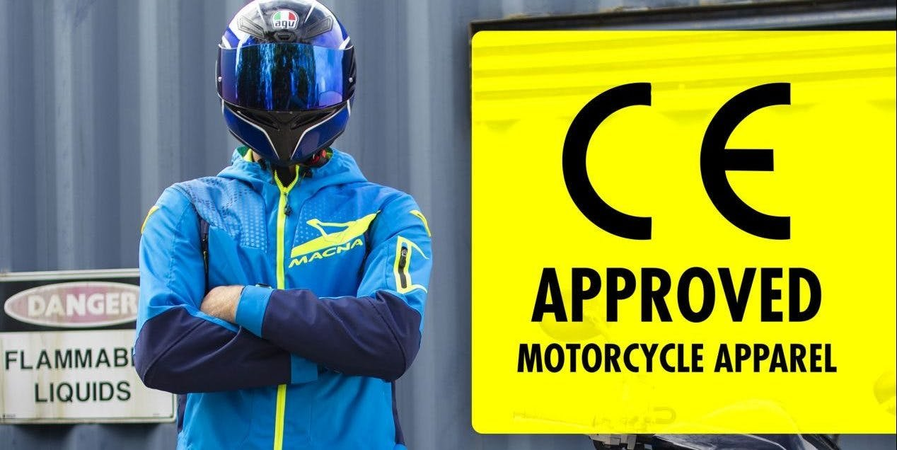 A guy in a AGV helmet and a blue Macna jacket next to a CE approved sign