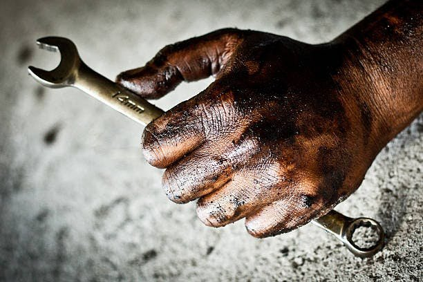 A greasy hand holding a spanner