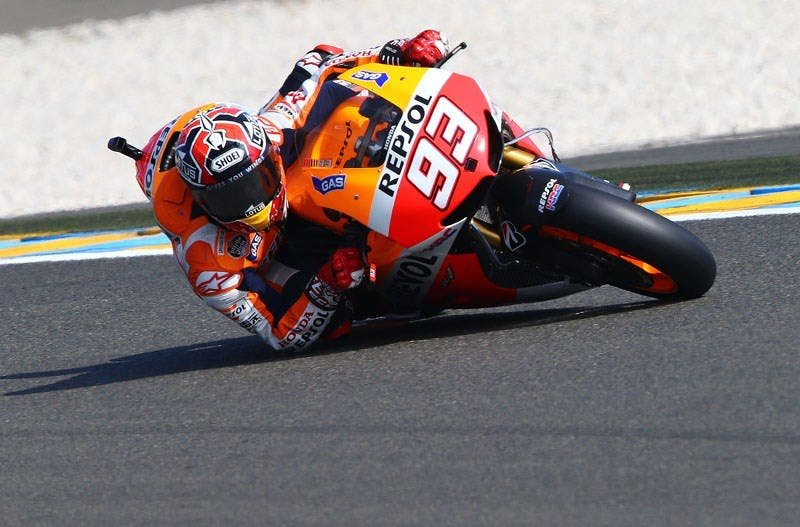 Marquez riding his motorcycle with his elbow on the track