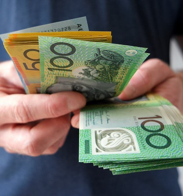 Hands with Australian $50 and $100 notes