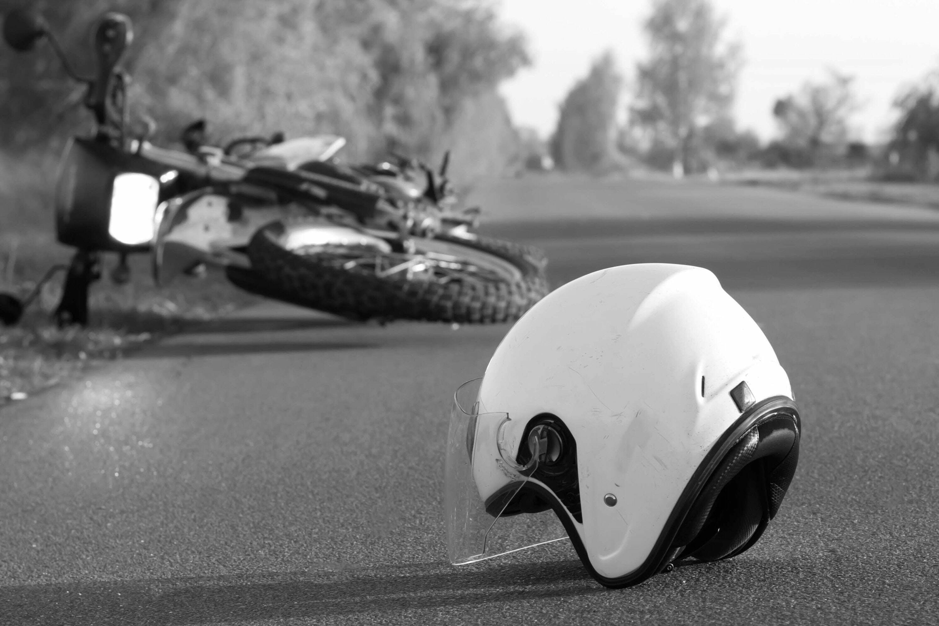 black and white picture of helmet and motorcycle on the side of the road