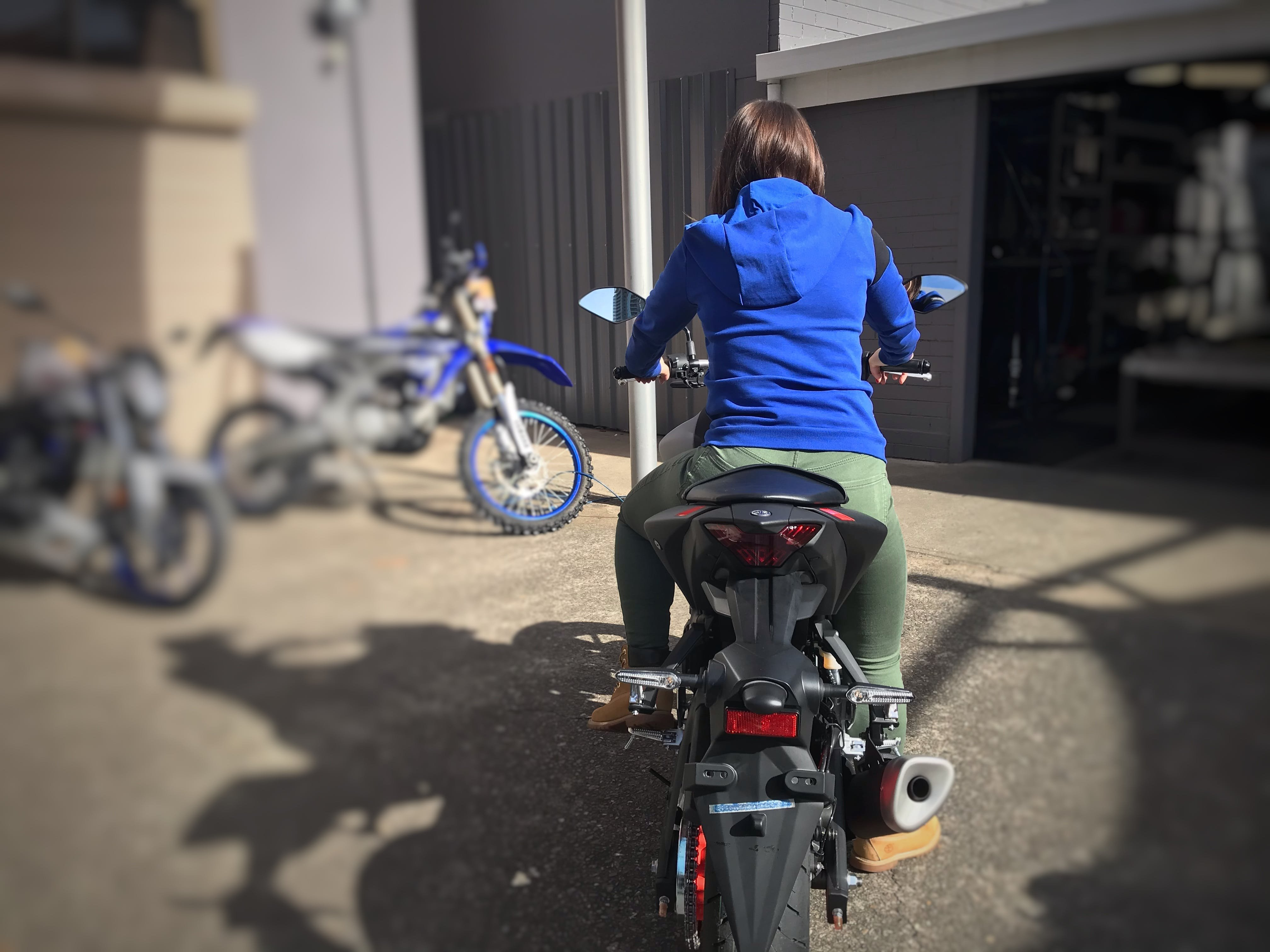 Woman in green pants sitting on a Yamaha MT03 in a car park