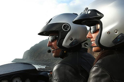 The Cardo Intercom System on a male rider with a dark silver open face helmet, and a female passenger with a light silver open face helmet