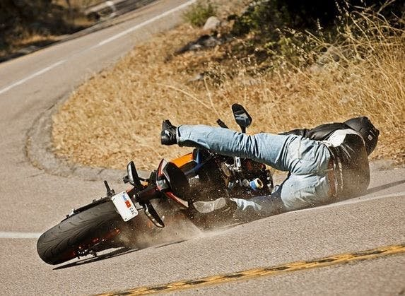 Man crashing on a motorcycle on the road