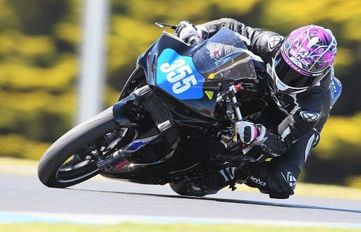 Woman on black motorcycle with pink helmet racing