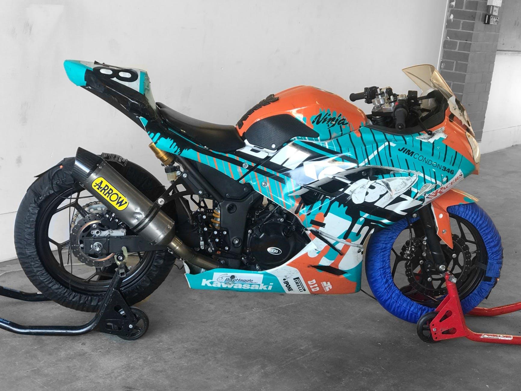 A blue and orange race Kawasaki Ninja 300 motorcycle