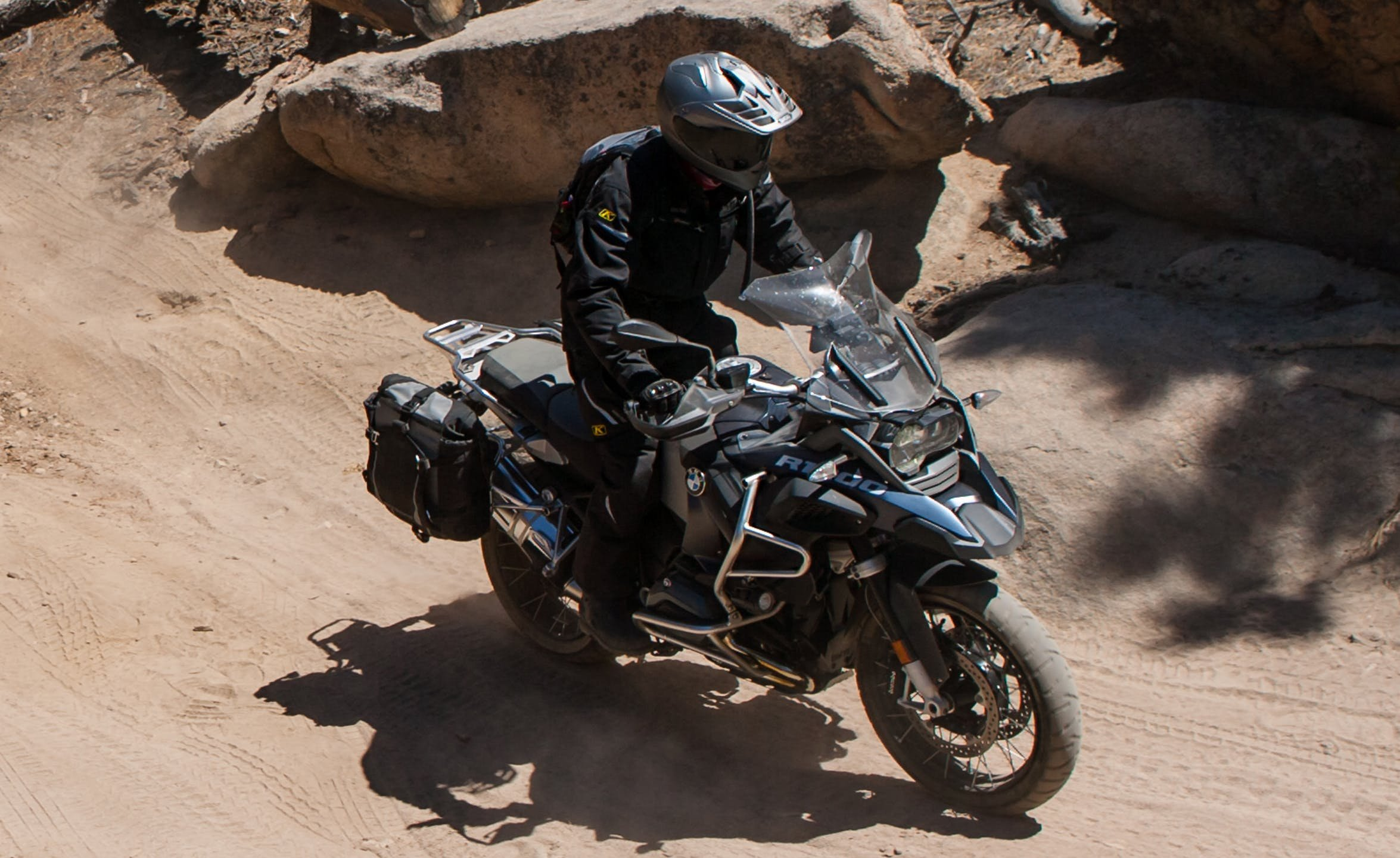 Adventure motorcycle rider on a BMW adventure motorcycle wearing all black protective gear