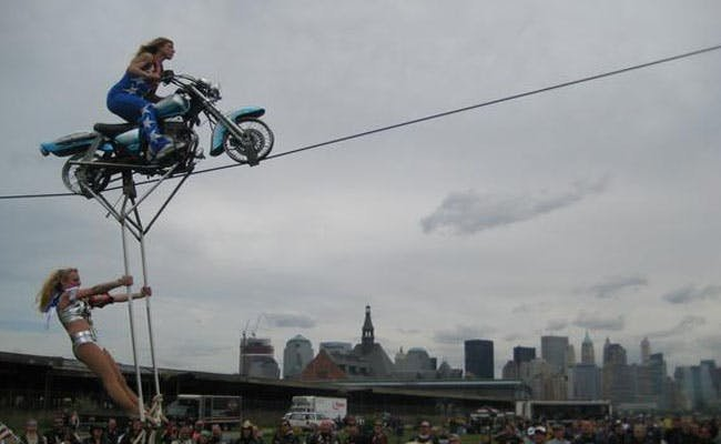 Motorcycle on a high wire with a woman hanging underneath