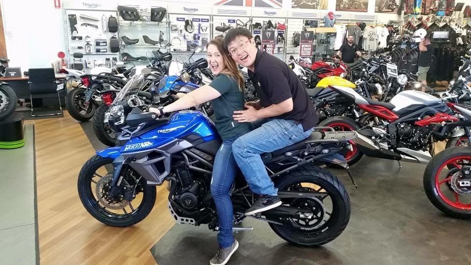 Short woman on a triumph tiger xox low adventure bike with a man on the back