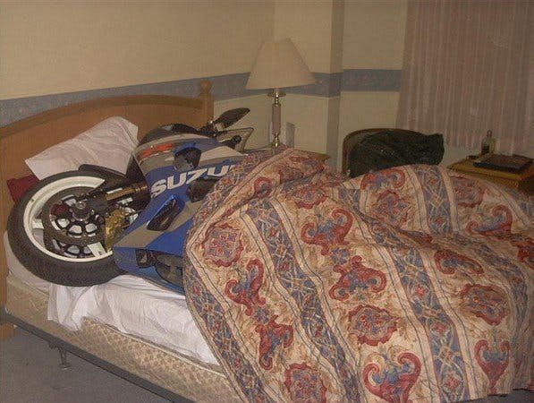 A motorcycle on a bed with a cover over it