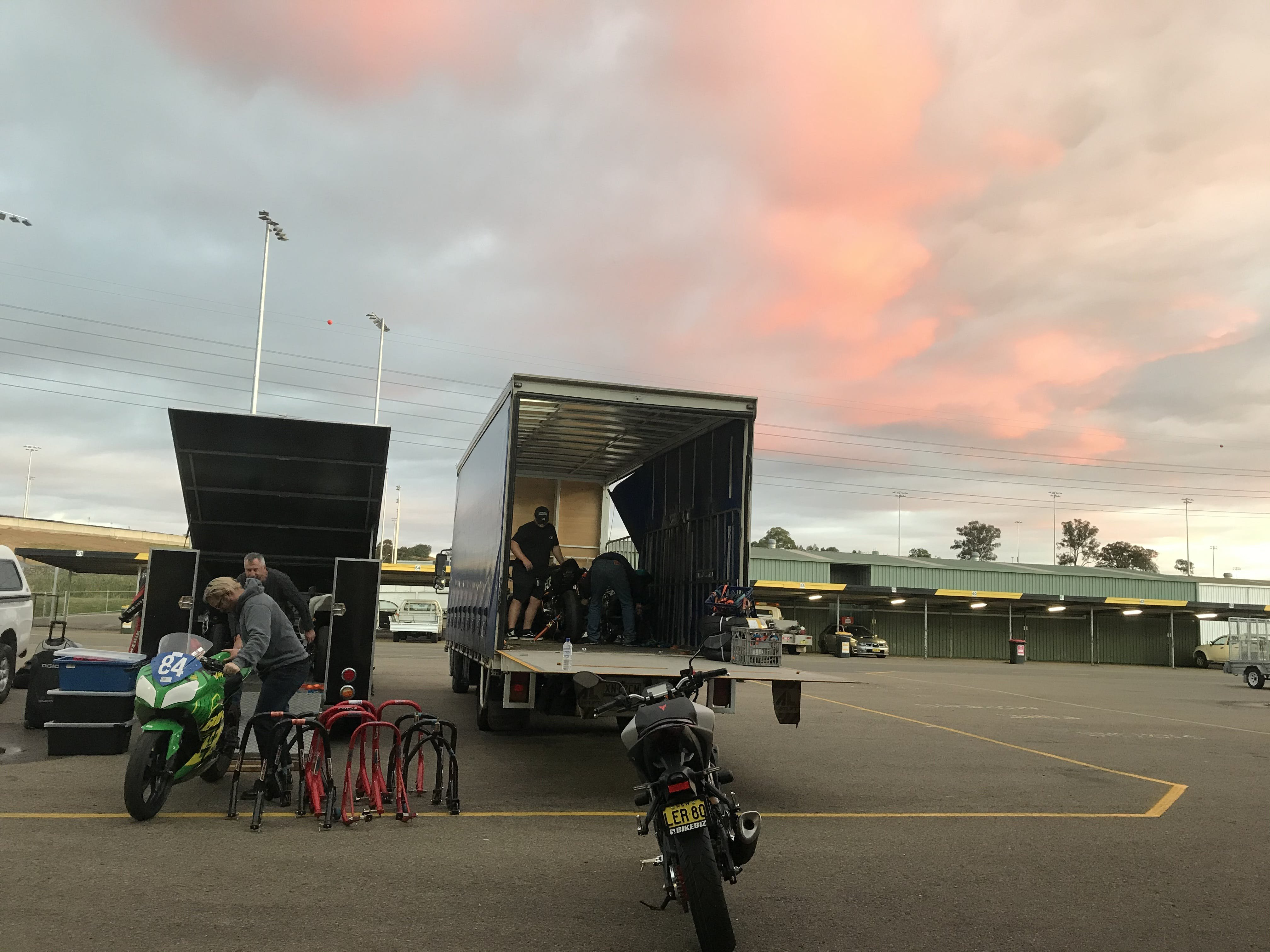 Motorcycles being loaded into a truck with a pink and blue sky background