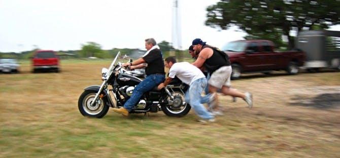 4 men push starting a cruiser motorcycle