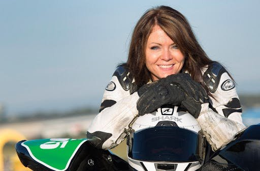 Brunette woman posing with helmet and motorcycle