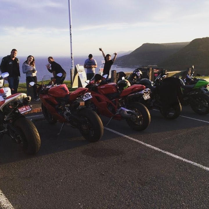 a group of motorcycle riders at the end of a ride