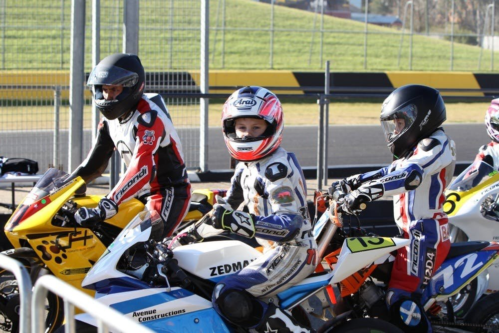 3 young boys on motorcycles in full protective gear at a racetrack