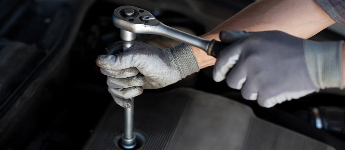 Gloved hands using a torque wrench