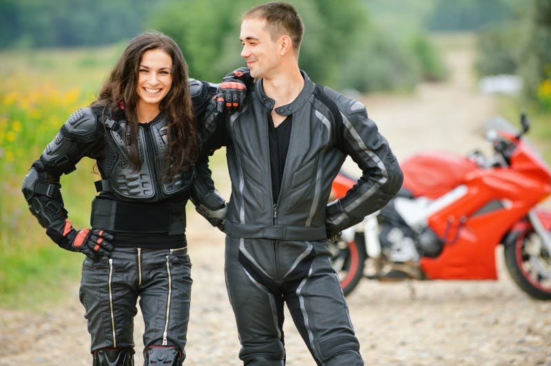 a happy couple in black leather in front of a red motorcycle