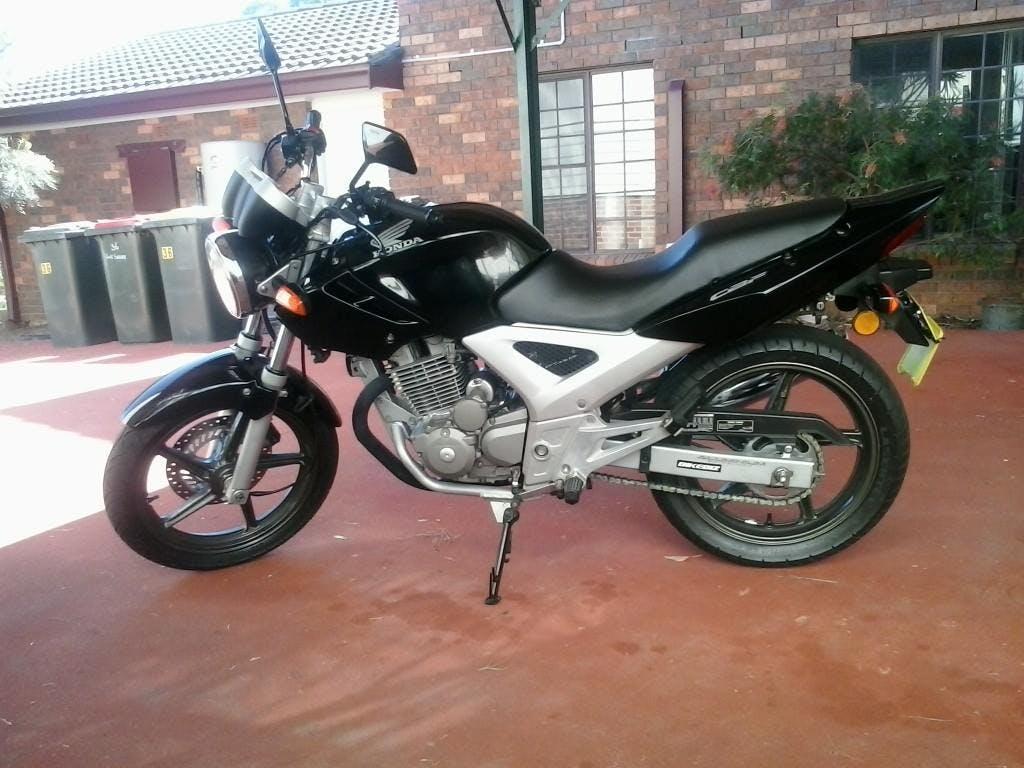 A black and silver Honda CBF250 motorcycle on an orange driveway