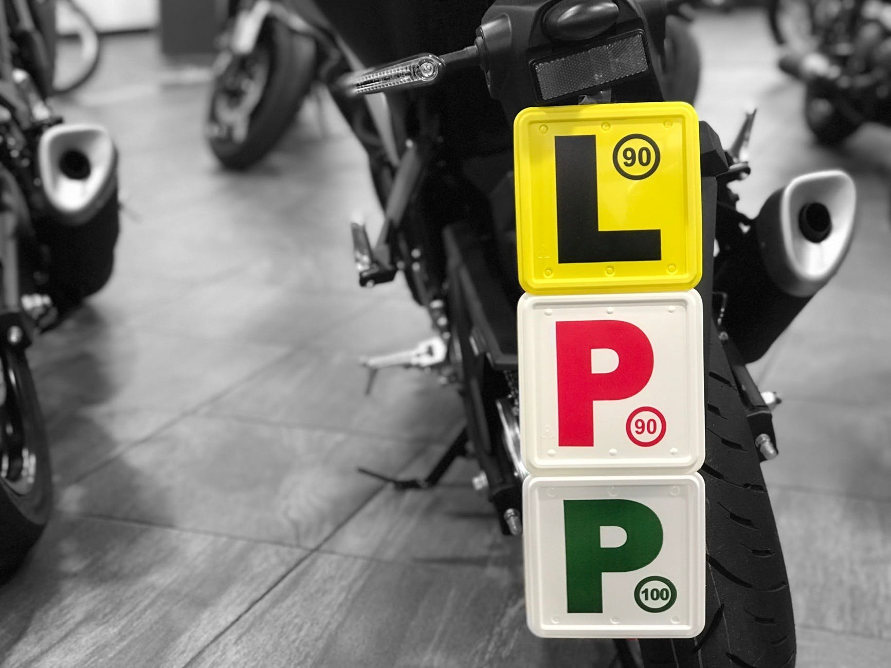 L, red P and green P plate all stuck together on the back of a motorcycle