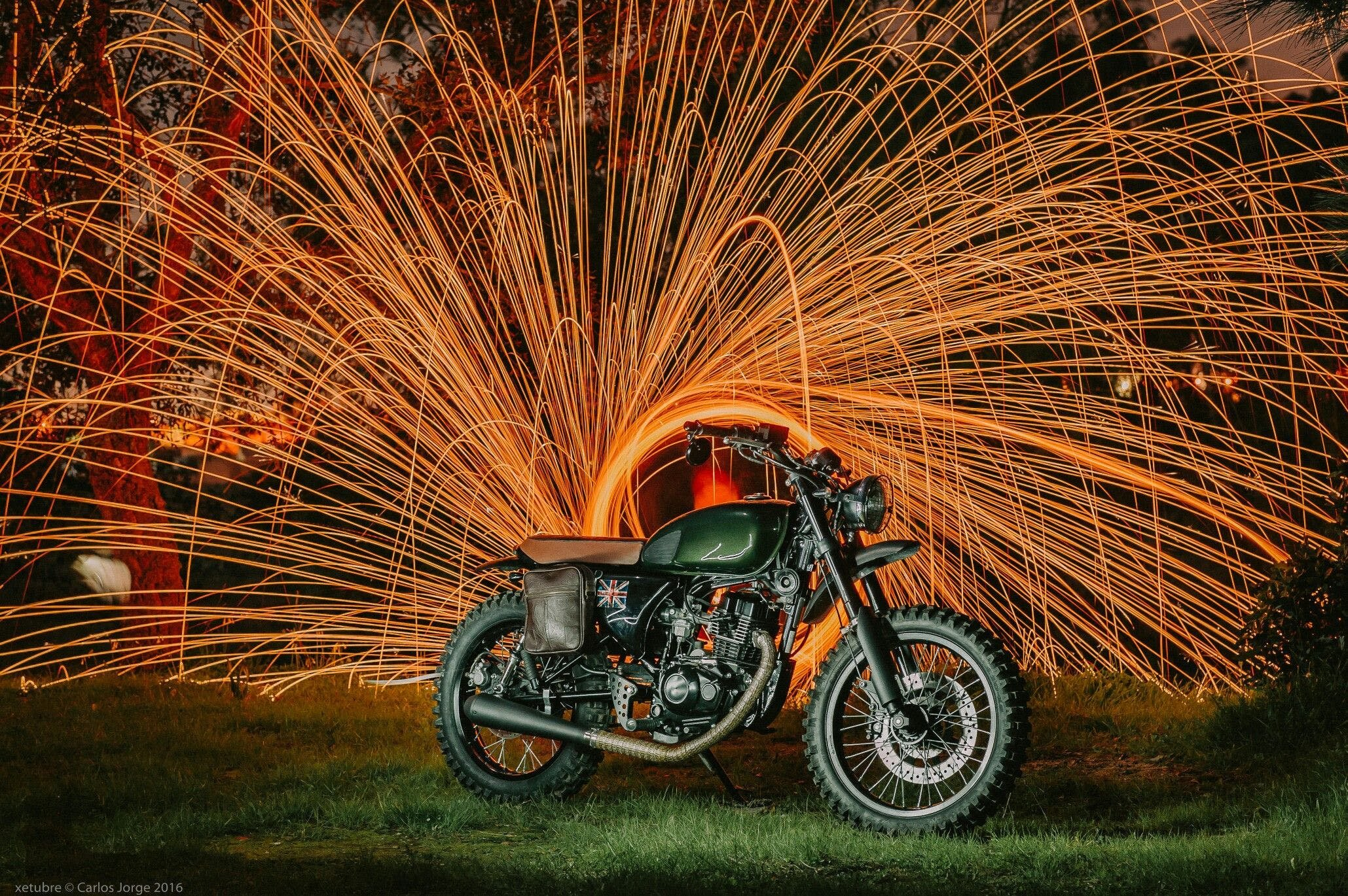 Old school motorcycle with orange fireworks in the background