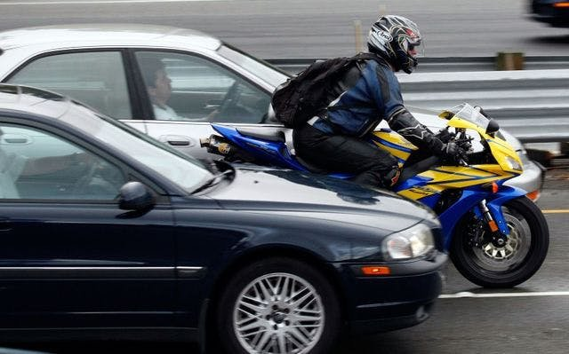 A motorcycle lane filtering in front of 2 cars
