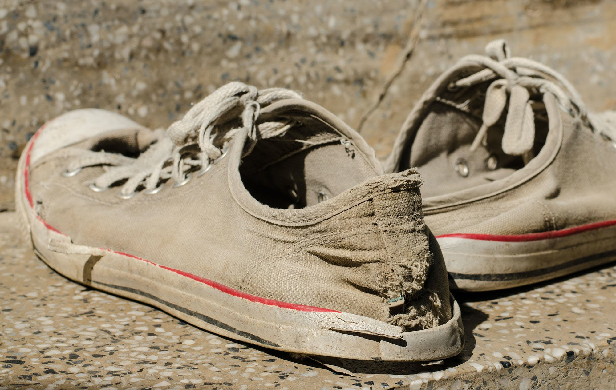 A pair of old sneakers with a hole in them