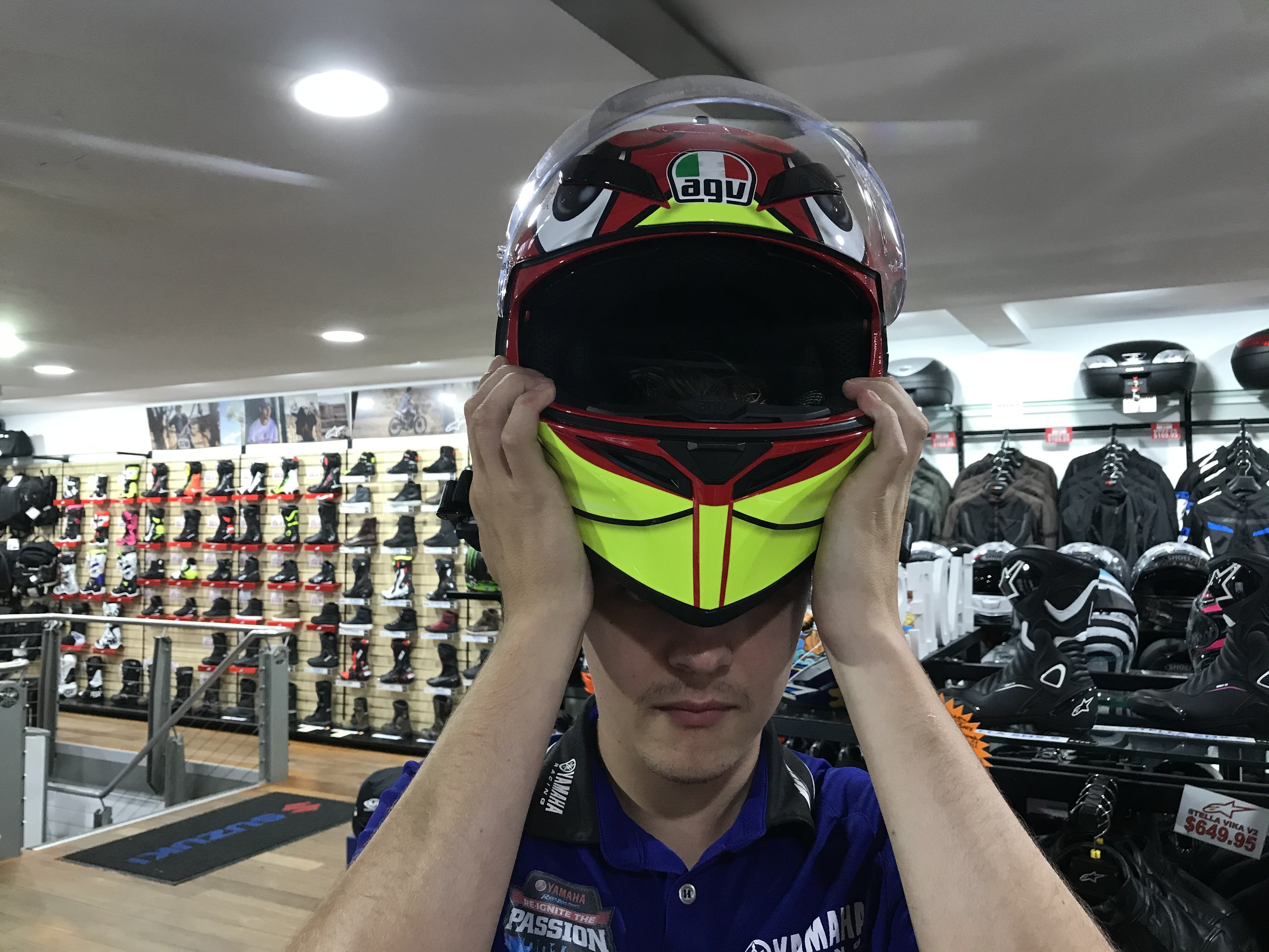 Guy putting on a red and yellow motorcycle helmet