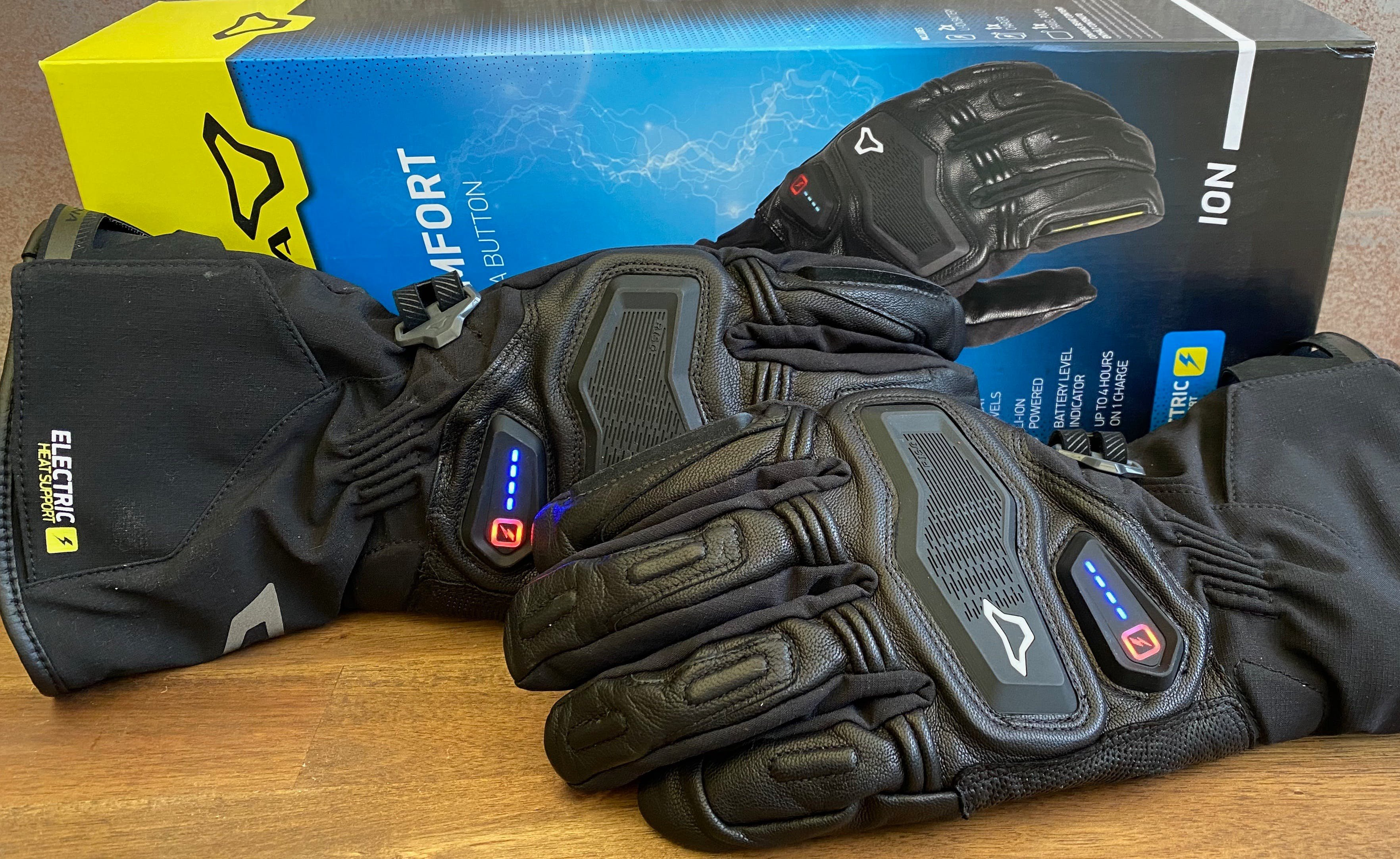 A pair of Macna Ion gloves in front of their blue and yellow box