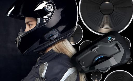 Cardo intercom system on a gloss black full face helmet on a blonde female