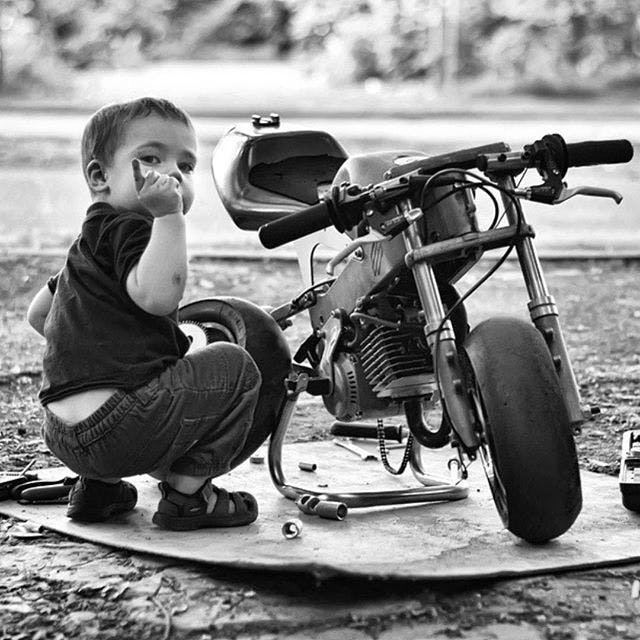 Small child fixing a small motorcycle