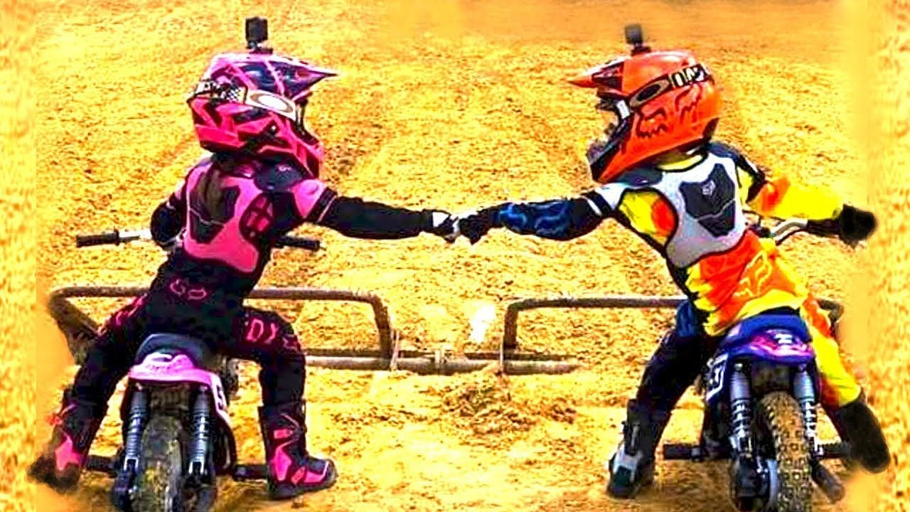 2 small kids fist bumping whilst on motorcycles