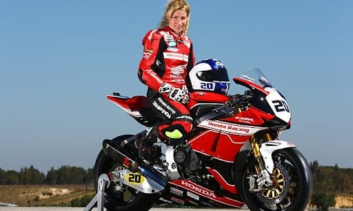 Jenny Tinmouth on a red motorcycle in red leathers