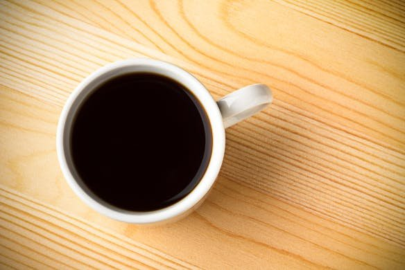 A cup of black coffee on a wooden surface
