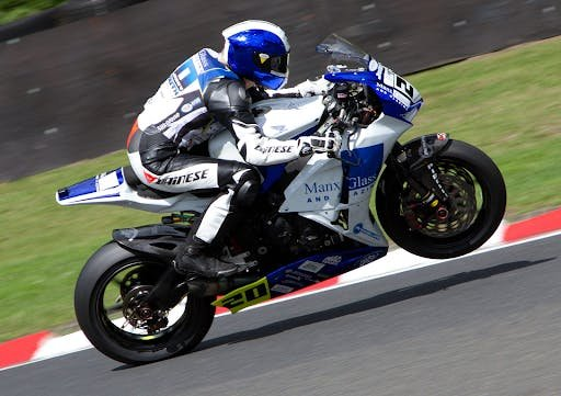 Jenny Tinmouth in blue and white leathers racing a blue and white motorcycle