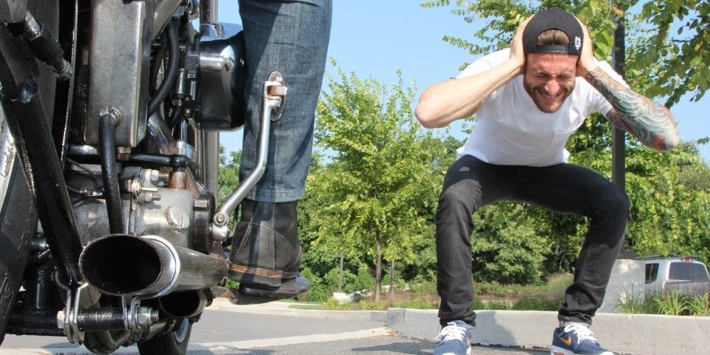 Guy covering his ears next to a motorcycle