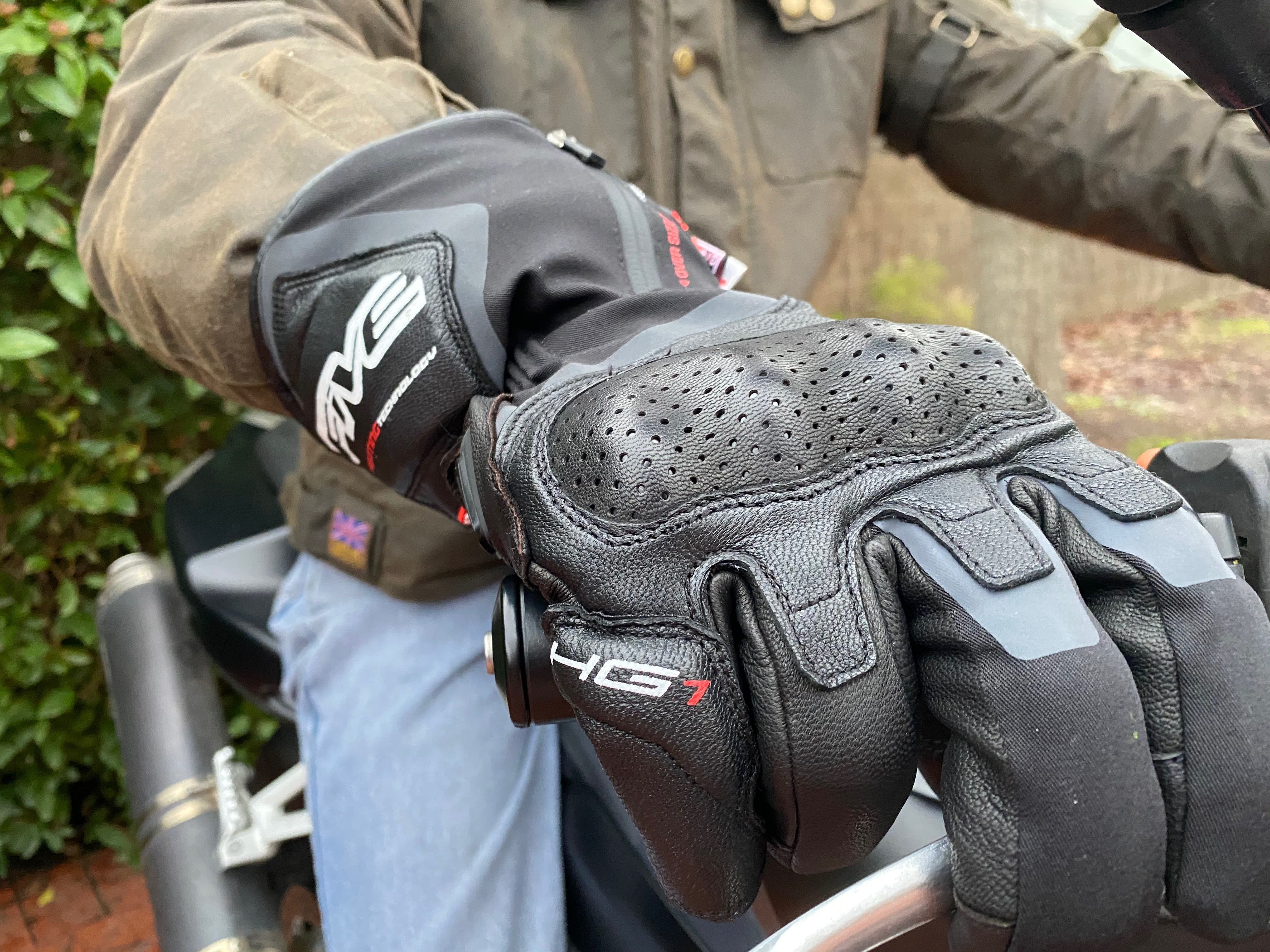 The Five HG-1 heated glove on a mans hand on a motorcycle handlebar