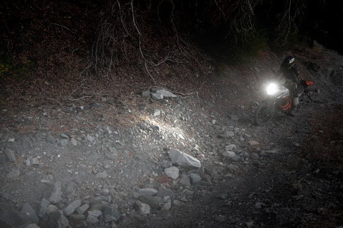 An adventure motorcycle on a dirt road with a bright headlight