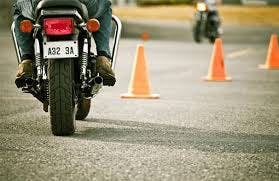 A motorcycle riding new orange traffic cones
