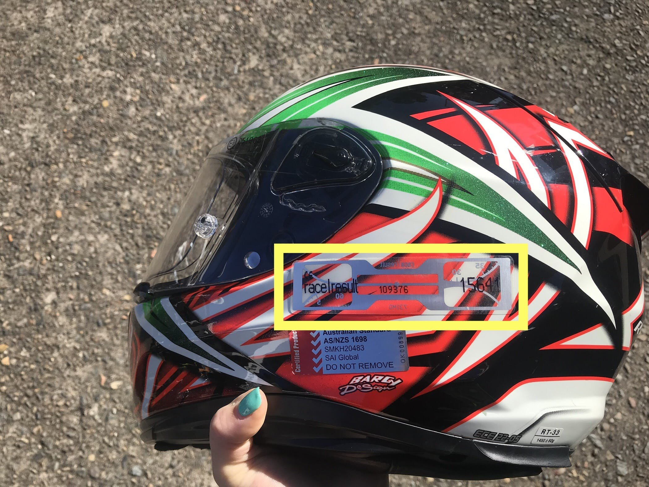 An orange and green Kabuto helmet with a SMSP time tracking sticker highlighted