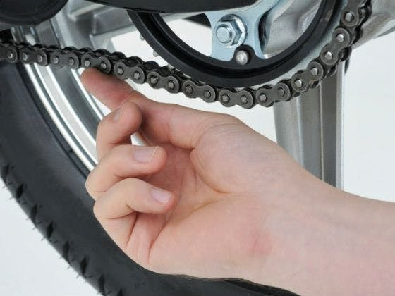 a hand checking the slack in a motorcycle chain